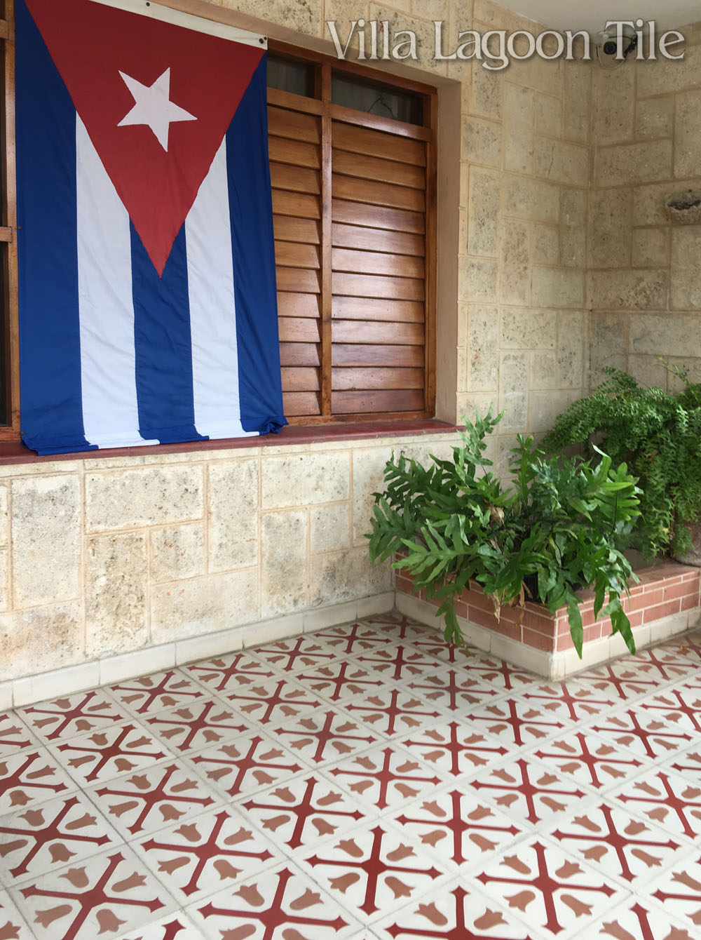 Cement tile on a front porch with a Cuban flag on display.